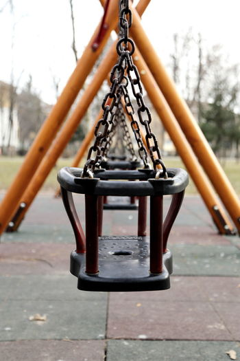 Close-up of empty swing in park against sky