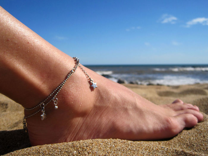 Low section of woman wearing anklet at beach against sky