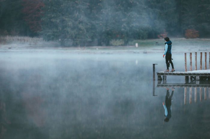 Man Standing On Pier Over Lake In Forest Pier Reflection Standing Adult Adventure Casual Clothing Day Extreme Sports Fog Full Length Leisure Activity Lifestyles Men Motion Nature One Person Outdoors People Real People RISK Side View Sport Standing Tree Water