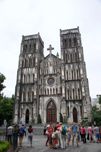 The Catholic Cathedral of Hanoi Cathedral Vietnam Architecture Belief Building Building Exterior Built Structure City Crowd Day Group Of People Hanoi Large Group Of People Men Place Of Worship Real People Religion Sky Spirituality Travel Destinations Visit Women