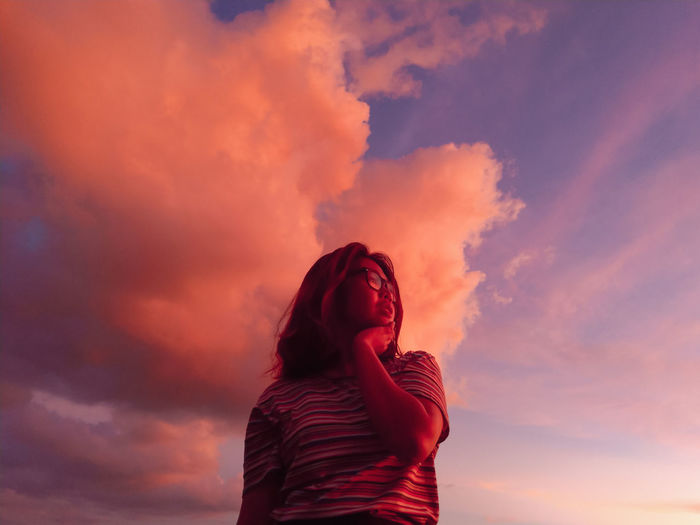 Low angle view of woman standing against orange sky