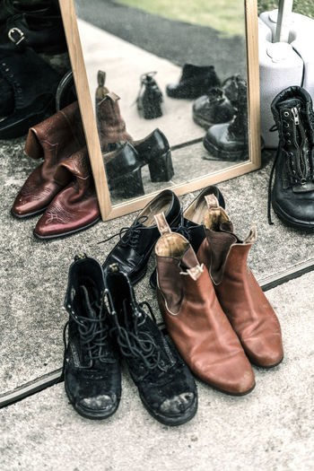 Shoes waiting for new homes at a Vintage Market Boots Heels Leather Market Mirror Reflection Second Hand Shopping Doc Martens Laced Boots Laces Leather Shoes Market Stall Old Boots Shoes Still Life Take Me Home Thrift Vintage Vintage Market Worn