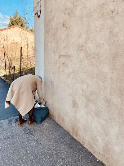 Rear view of man sitting on wall