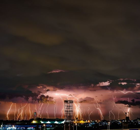 Illuminated buildings in city against sky at night with massive lightning strikes