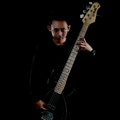 Portrait of man playing guitar against black background