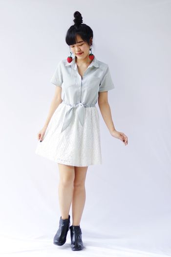 Full length portrait of woman standing against white background