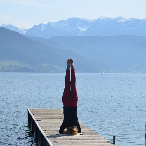 Woman Exercising On Pier Over Lake Against Mountains