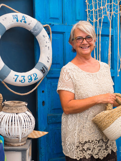 Portrait of smiling senior woman standing against blue door