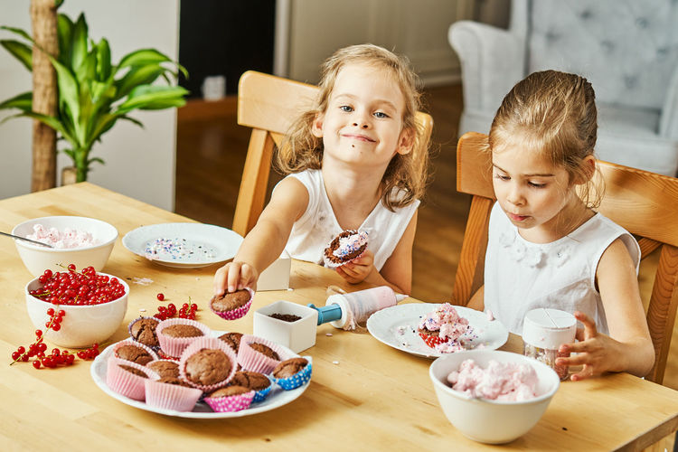Muffin Muffins Girl Child Kid Childhood Twins Sister Sisters Food And Drink Table Food Girls Sitting Real People Women Two People Togetherness Indoors  Females Refreshment Portrait Drink Lifestyles Sweet Food Family Freshness Meal Breakfast