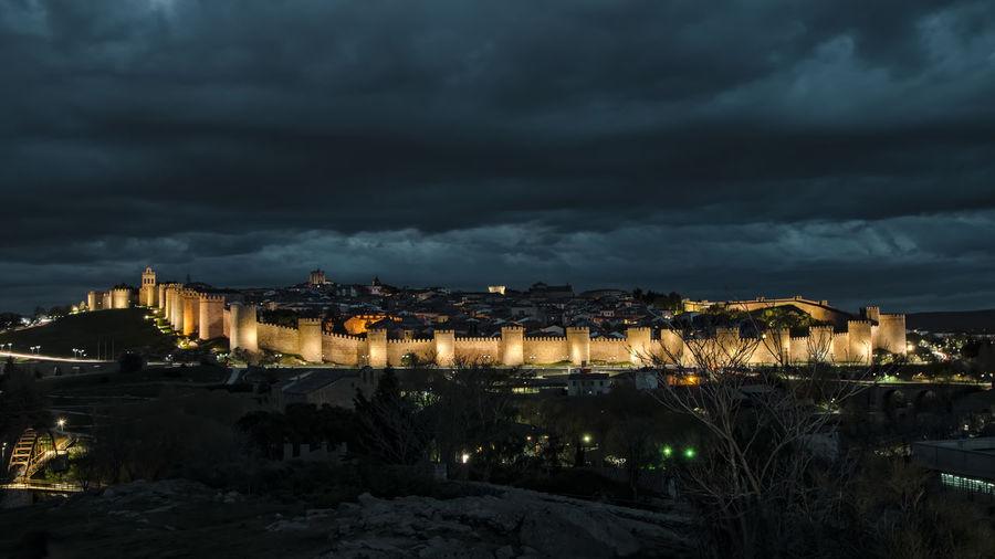 Illuminated City Against Cloudy Sky At Night