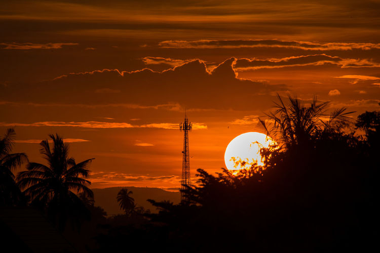 Silhouette of communications tower against at sunset