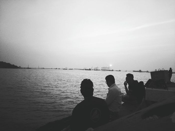 Rear view of people sitting on beach against clear sky