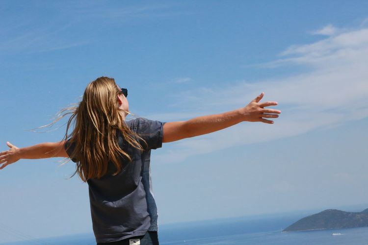 Rear view of woman with arms outstretched by sea against sky