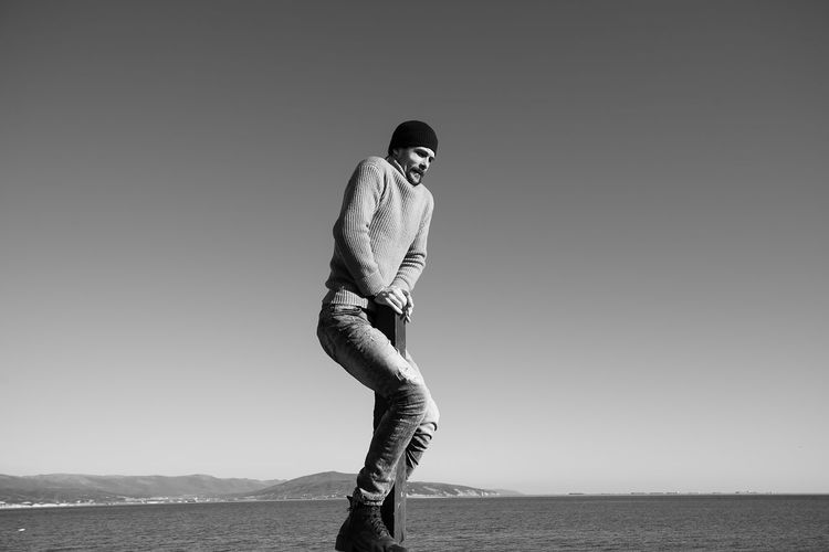 A young man does something interesting. It interacts with a wooden pile on the seashore. One person in the frame. Man on the background of a clear sky. He is warmly dressed in boots, jeans, a sweater and a hat. Casual wear. The guy wears a mustache and stubble. Hair out of the caps. Winter sunny day. Live black and white photo. Lifestyles Lifestyle Authentic Moments Authentic Candid Real People Blackandwhite Black And White One Person Sky Leisure Activity Clear Sky Men Full Length Standing Young Men Day Water Casual Clothing Sea Nature Tranquil Scene Tranquility Scenics - Nature Motion