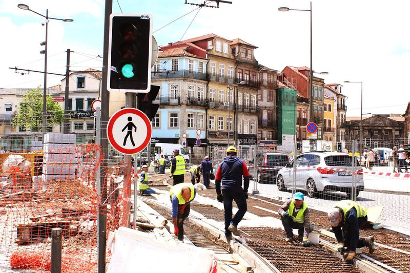 Men working on road against buildings during sunny day
