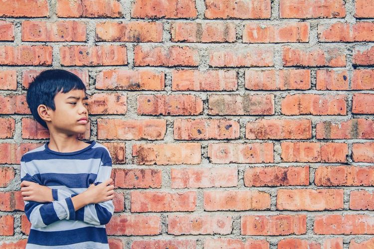 Breathing Space Brick Wall Child Childhood Children Only Depression - Sadness Males  Copy Space Boys One Person People Distraught  Elementary Age Red Human Body Part One Boy Only Lifestyles Outdoors Day Visual Creativity