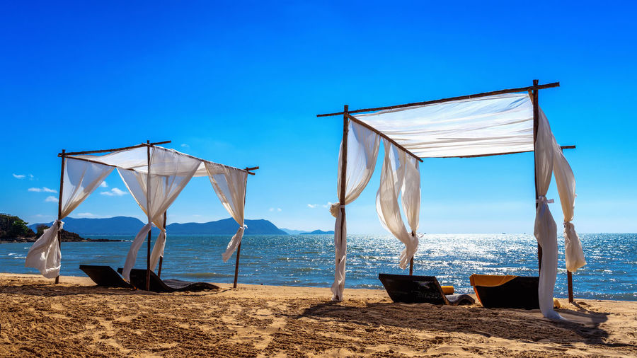 Beach canopies with sun loungers on beach. Water Sky Beach Sea Land Scenics - Nature Sand Nature Blue Beauty In Nature Day Horizon Over Water Horizon Clear Sky Nautical Vessel Tranquility Sunlight No People Textile Outdoors Sailboat