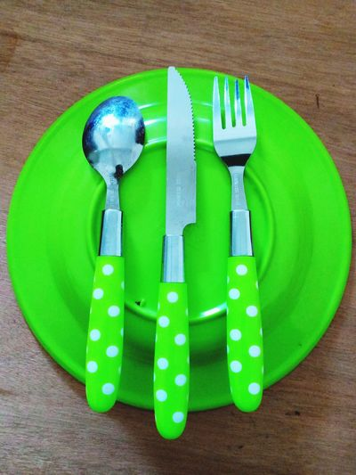 High angle view of green plate with cutlery on table