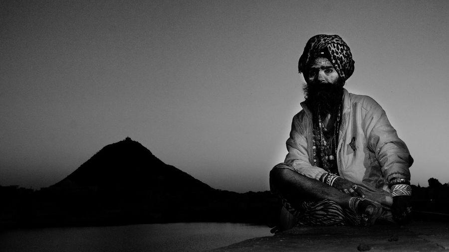 Sadhu sitting by lake against mountains