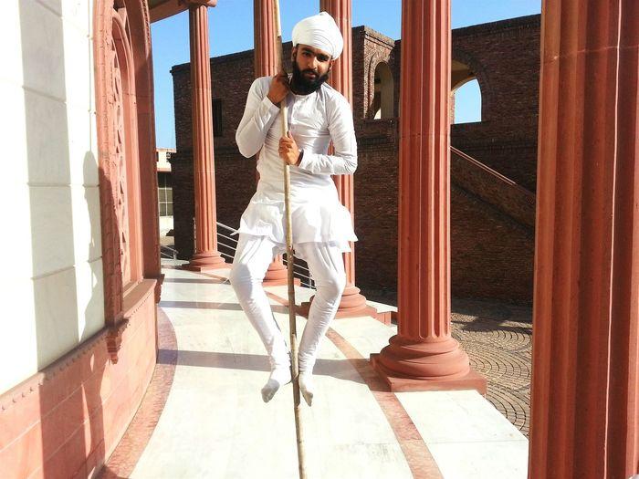 Young Man Wearing Turban Balancing On Stilt