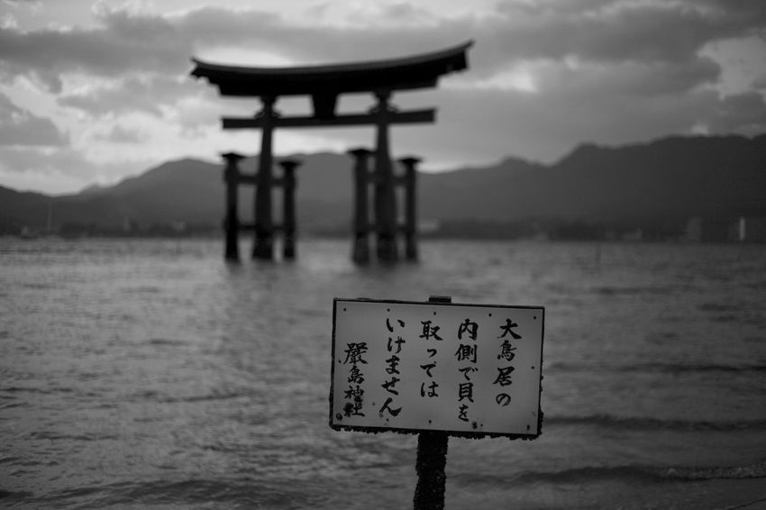 Japan Miyajima Beauty In Nature Cloud - Sky Communication Day Focus On Foreground Mountain Nature No People Outdoors Religion Scenics - Nature Sea Sign Sky Text Tranquil Scene Tranquility Water