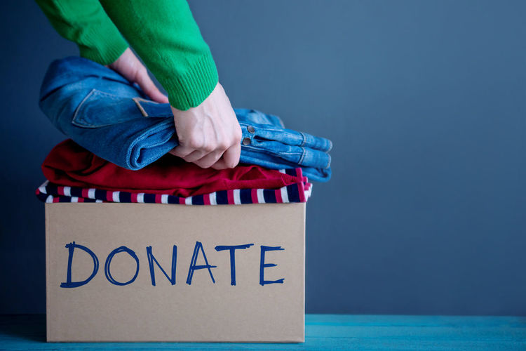 Cropped Hands Of Woman With Clothes In Box With Donate Text