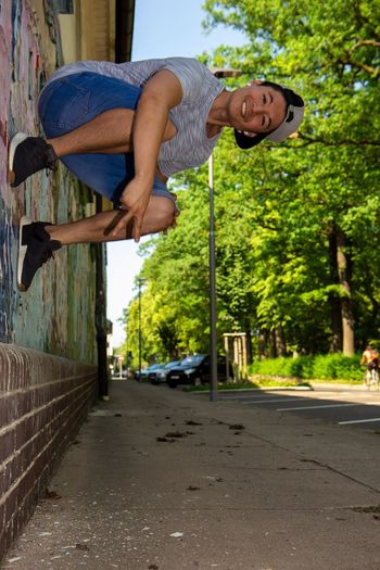 Optical Illusion Of Man Sitting On Wall Against Trees