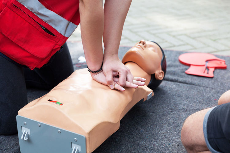 Midsection of paramedics practicing on cpr dummy at blanket