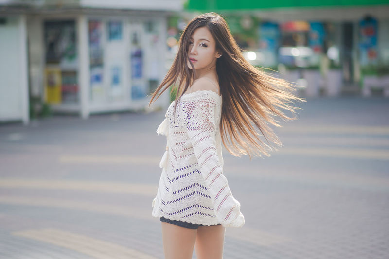 Beautiful young woman standing at parking lot