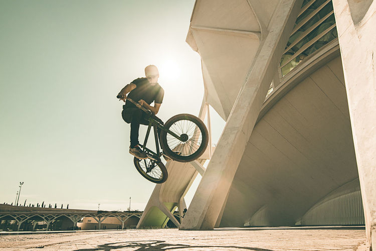 Low angle view of man riding bicycle on bridge