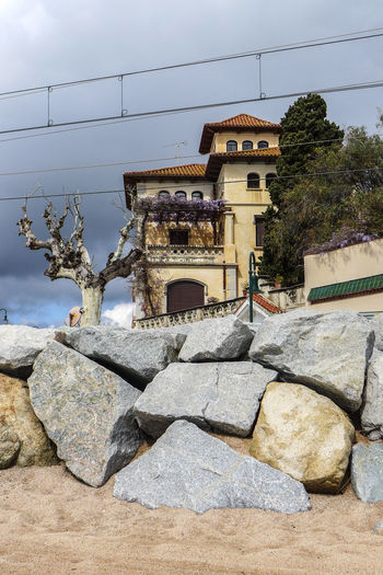 Architecture Beach Scene  Blue Beige Grey Building Exterior Built Structure Cable Composition Railway View Stone Wall Sunlight Train Line Tree Wall - Building Feature