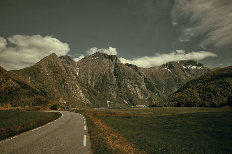 Country road amidst mountains against sky