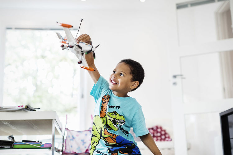 Boy holding toy while standing at home