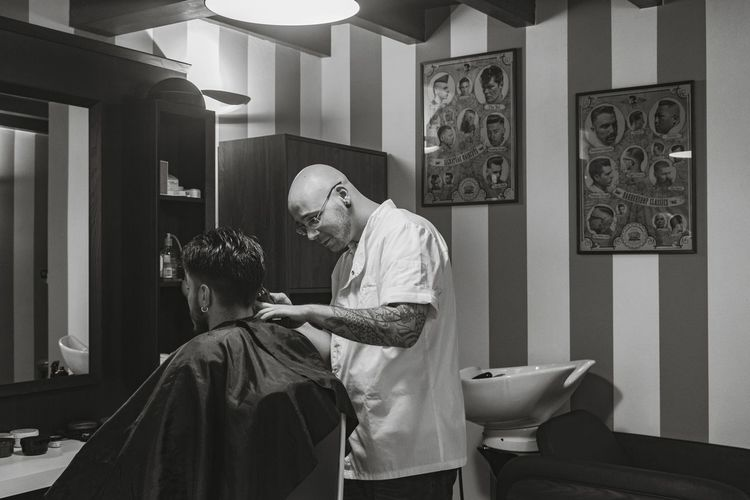 Side view of barber cutting man hair in salon