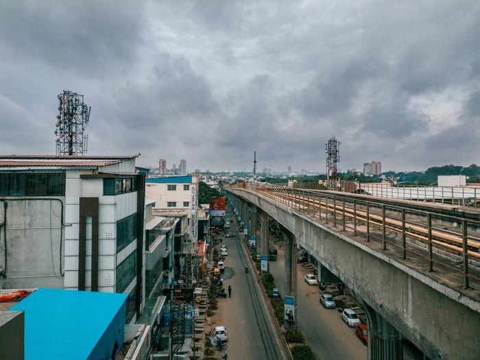 Railway bridge by buildings in city against cloudy sky