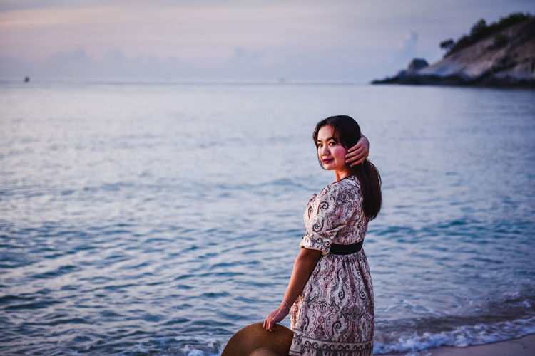 Portrait of smiling woman standing in sea