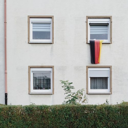 Hedge And Four Windows Of Residential Building With German Flag In One Window