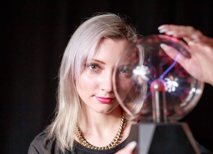 Close-up portrait of young woman holding plasma ball over black background