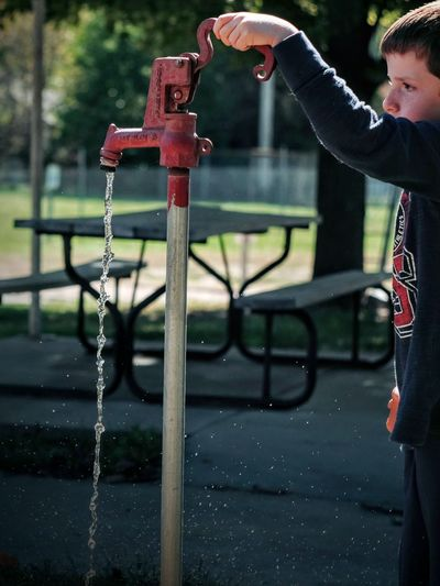 Cropped image of boy holding tap while standing in park