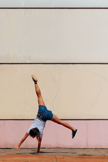 Full length rear view of woman practicing handstand against wall