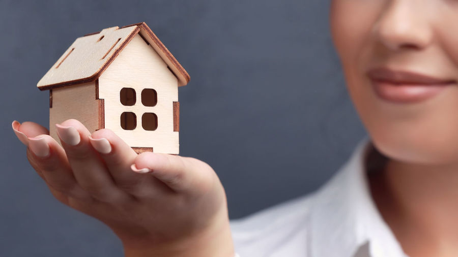 Close-up of woman holding hands by house in building