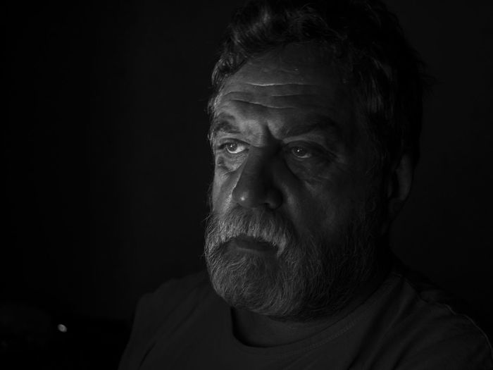 Close-up of serious senior man against black background