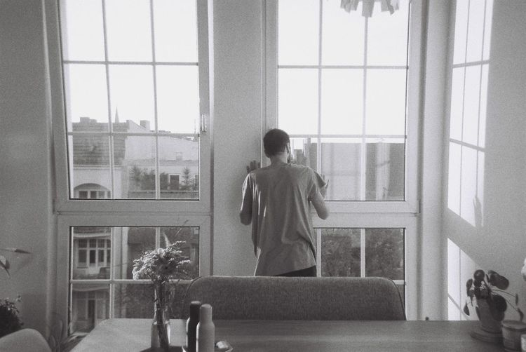 Rear view of shirtless man standing against window at home