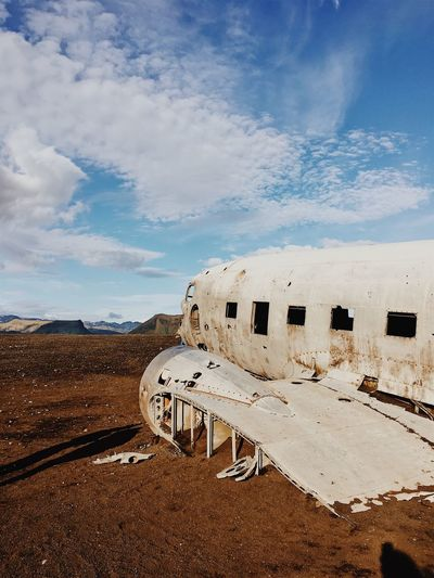 Abandoned Airplane On Landscape Against Sky