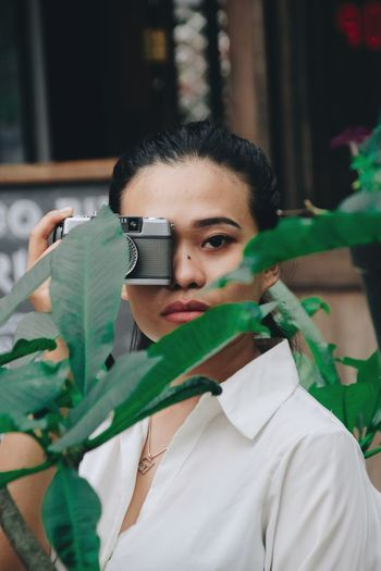 Portrait Of Young Woman With Camera Seen Through Plant