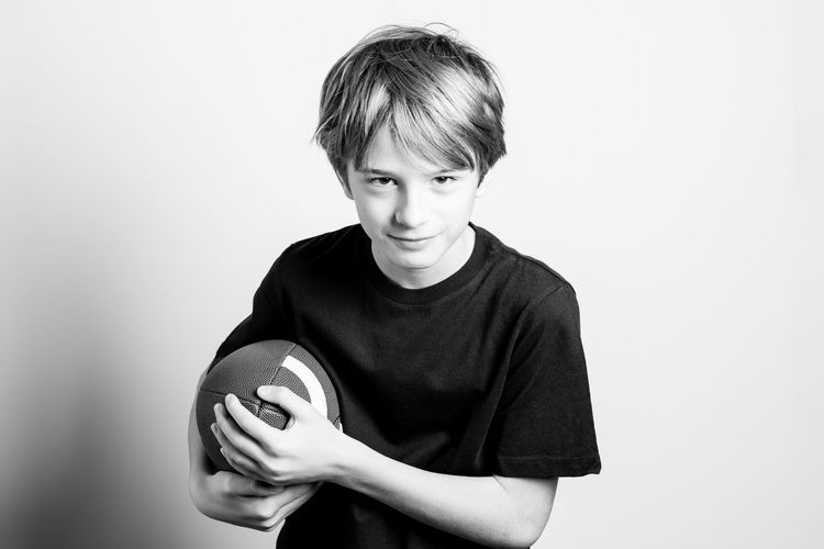 Portrait Of Teenage Boy Holding Rugby Ball Against White Background