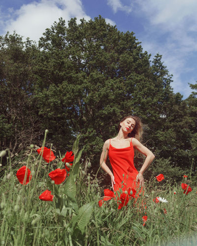 Woman standing by red poppy flowers on field