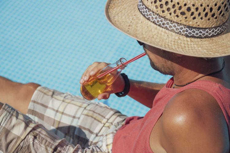 Man drinking juice in bottle by poolside