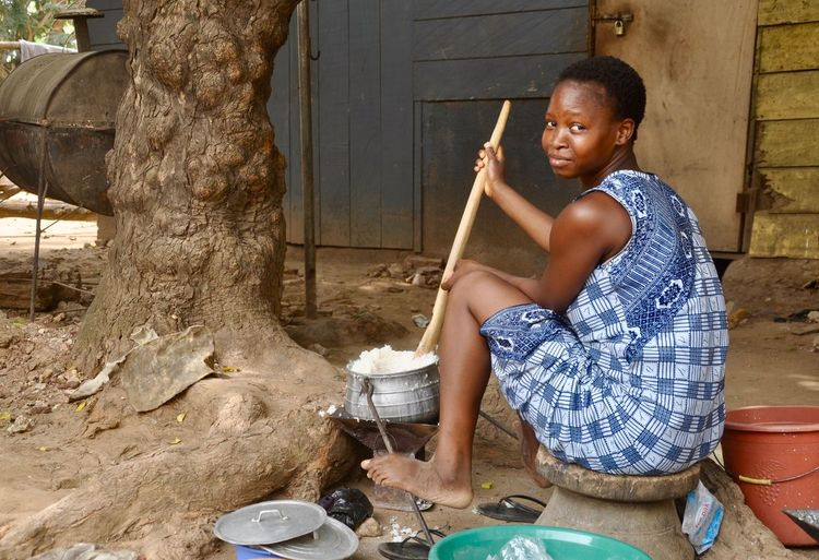 Portrait of young woman preparing food while sitting outdoors