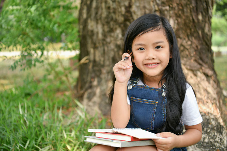 Portrait Of Smiling Girl With Books Sitting On Grassy Field Against Tree At Park